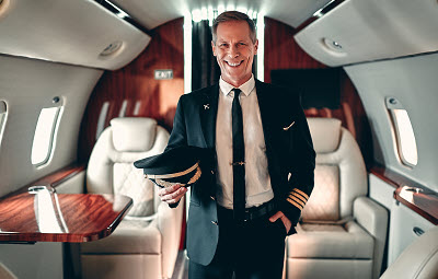 Experienced pilot in uniform standing in cabin of private jet
